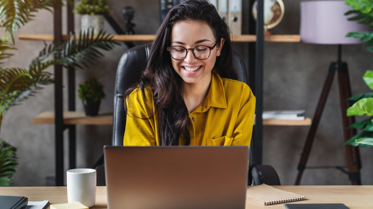 Young happy cute business woman sit indoors in home office using laptop computer